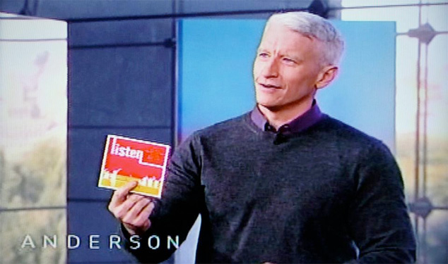 Anderson Cooper holding Our Time's Benefit Album, Listen, on his daytime talk show.